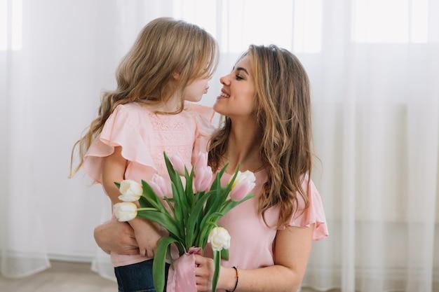 Szczęśliwego dnia matki. córka dziecka gratuluje mamom i daje jej kwiaty tulipanów.