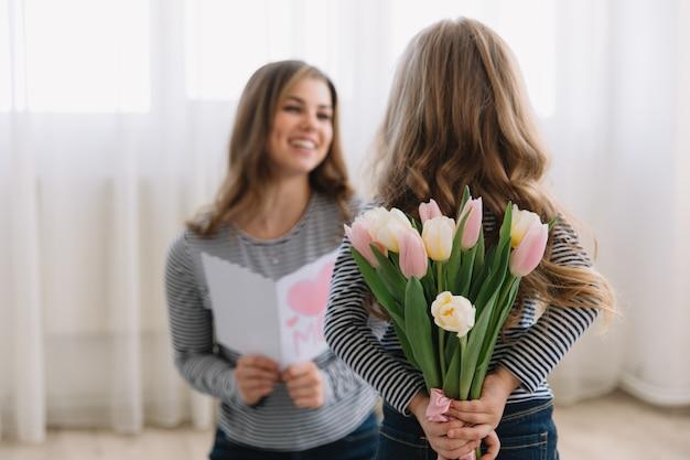 Szczęśliwego dnia matki. córka dziecka gratuluje mamom i daje jej pocztówkę i kwiaty tulipanów.
