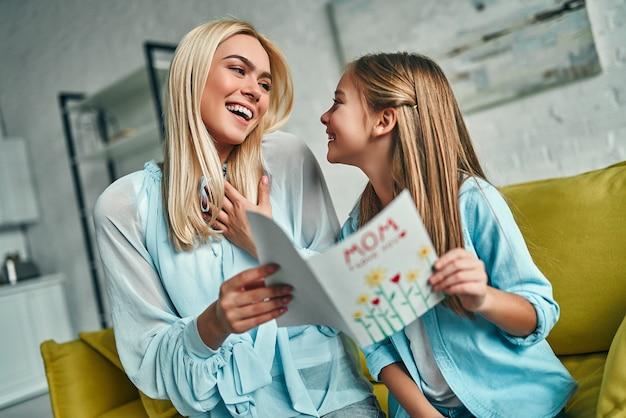 Szczęśliwego dnia matki! córka gratuluje mamie i daje jej pocztówkę. mama i dziewczyna uśmiechając się i przytulając. rodzinne wakacje i razem.