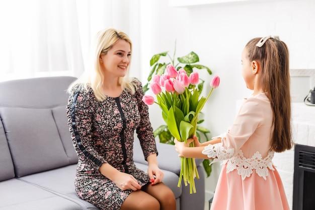 Szczęśliwego dnia matki. córka gratuluje mamom i daje jej kwiaty tulipany