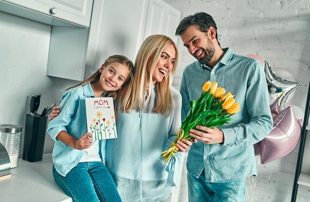 Szczęśliwego dnia matki! córka z tatą gratulują mamie i dają jej kwiaty tulipany i pocztówkę. mama uśmiecha się i przytula. rodzinne wakacje i razem.