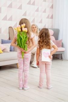 Szczęśliwego dnia matki. córki dzieci gratulują mamie i dają jej pocztówkę oraz bukiet kwiatów tulipanów w różowym salonie w ich domu.