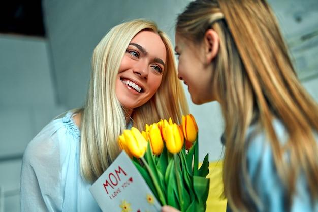 Szczęśliwego dnia matki! mała dziewczynka daje bukiet matce. córka gratulująca mamie pięknych wiosennych kwiatów na dzień matki