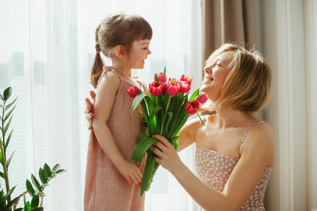 Szczęśliwego dnia matki! mała dziewczynka gratulując matce i dając jej kwiaty. mama i córka uśmiechając się i spędzając czas razem. skoncentruj się na tulipanach.