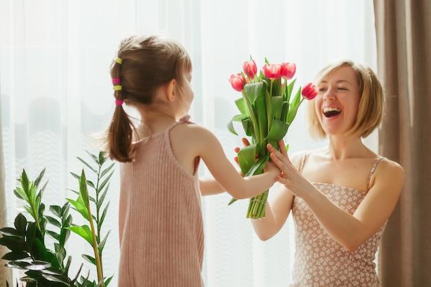 Szczęśliwego dnia matki! mała dziewczynka gratulując matce i dając jej kwiaty. szczęśliwa mama i córka spędzają czas razem. skoncentruj się na tulipanach.