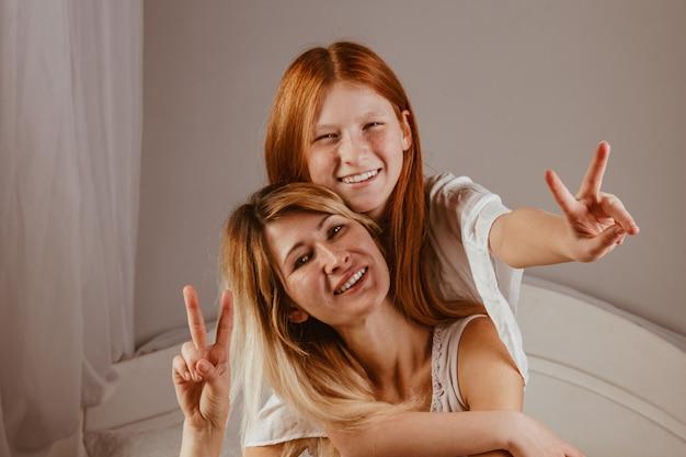Szczęśliwego dnia matki. mama i jej córka grają w dziewczynę, uśmiechając się i przytulając do łóżka. rodzinne wakacje i wspólnoty.