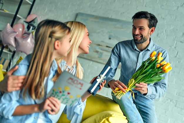 Szczęśliwego dnia matki! ojciec gratuluje mamie i daje jej prezent oraz kwitnie tulipany.
