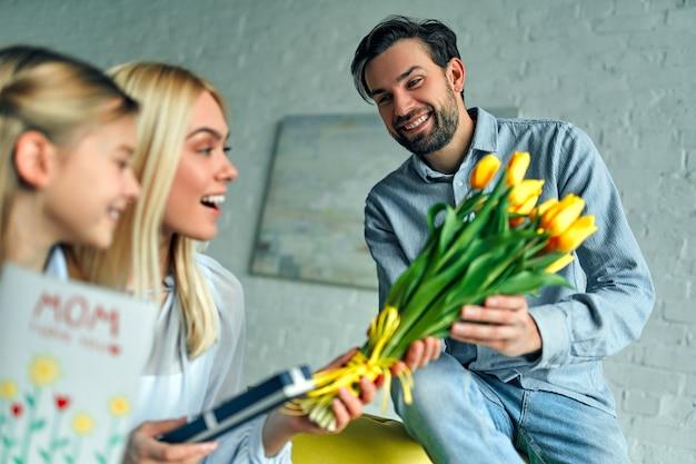 Szczęśliwego dnia matki! ojciec gratuluje matce wakacji i daje jej prezent i kwitnie tulipany.