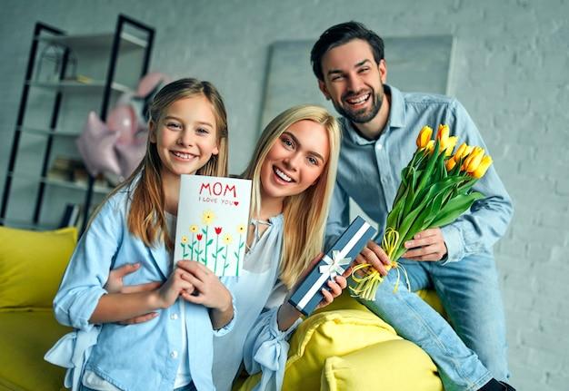 Szczęśliwego dnia matki! ojciec i córka gratulują mamie wakacji i dają jej pocztówkę oraz kwiaty tulipanów.