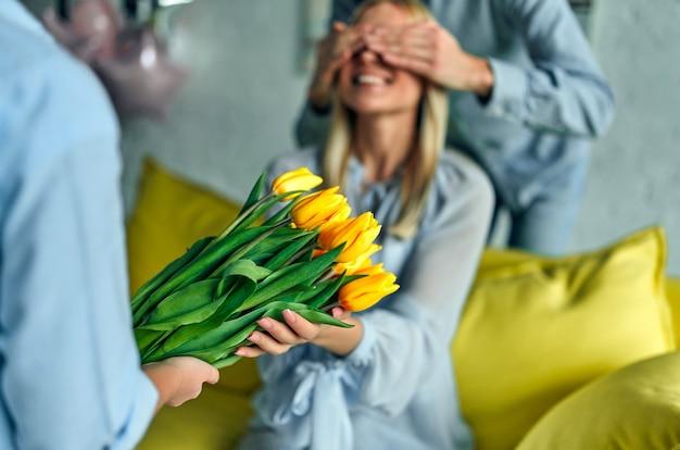 Szczęśliwego dnia matki! ojciec i córka gratulują matce wakacji i dają jej kwiaty tulipany.