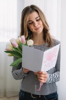 Szczęśliwego dnia matki. piękna kobieta czytania pastcard z córką i trzymając tulipany.