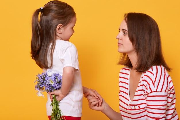 Szczęśliwego dnia matki! słodkie dziecko dziewczynka gratuluje matce na wakacjach i chce dać kwiaty.