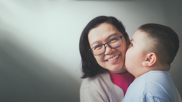 Szczęśliwego dnia matki! syn dziecka gratuluje matce i całuje ją w policzek.