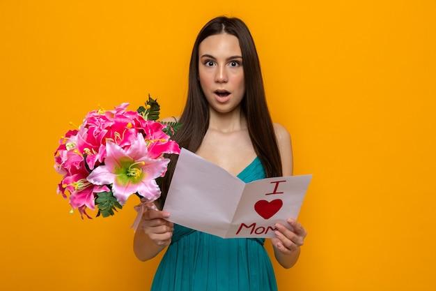 Szczęśliwego dnia matki. zaskoczony piękna młoda kobieta trzyma kartkę z życzeniami i bukiet
