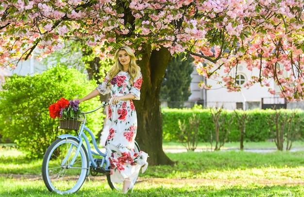 Szczęśliwego dnia wiosny. młoda modna dziewczyna z retro rowerem w pobliżu kwitnących wiśni. dziewczyna z rocznika roweru w alei różowy sakura. kwitnące drzewo na wiosnę. naturalne kobiece piękno. kobieta w ogrodzie.