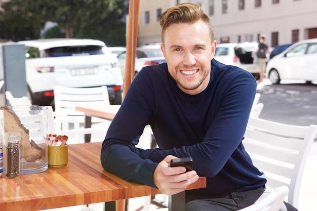 Szczęśliwego faceta siedzący outside przy kawiarnią z telefonem komórkowym