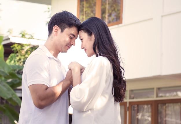 Szczęśliwego i pełnego nadziei caucasian mężczyzna mienia ręki młodej kobiety pary azjatykcia pozycja przy frontowym jardem nowy dom lub przeniesienie po pojęcia leasingu lub finanse.
