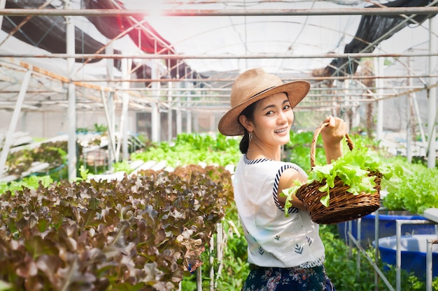 Szczęśliwego i piękna azjatykcia kobieta trzyma sałatkowych warzywa koszykowych w gospodarstwie rolnym