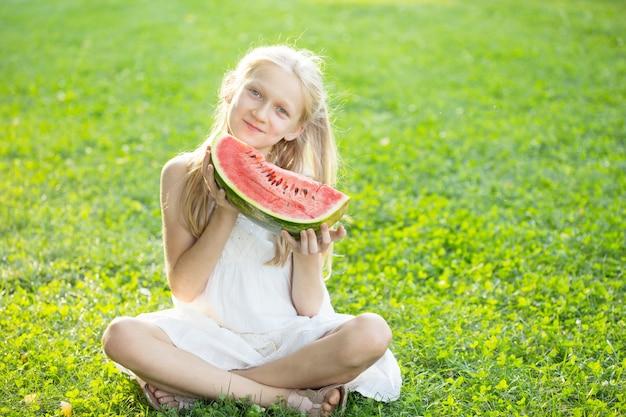Szczęśliwego lata - piękna blond dziewczynka je arbuza na zielonym trawniku