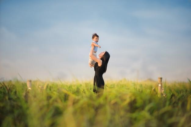 Szczęśliwego macierzystego chwyta szczęśliwy mały dziecko w zielonym ryżu polu przy kraj stroną thailand.