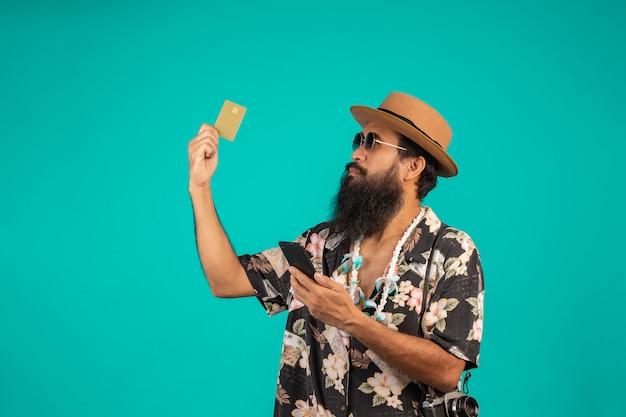 Szczęśliwego mężczyzny z długą brodą w kapeluszu, koszuli w paski i złotej karty kredytowej na niebieskim.