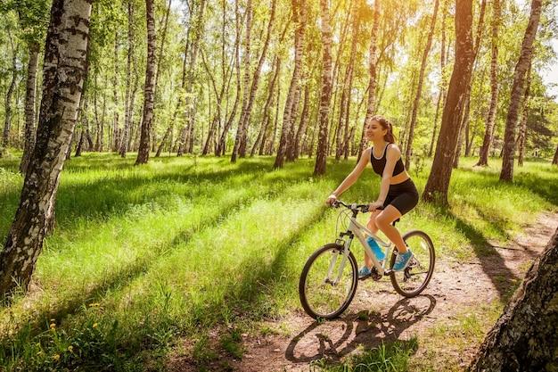 Szczęśliwego młoda kobieta cyklisty jeździecki bicykl w wiosna lesie