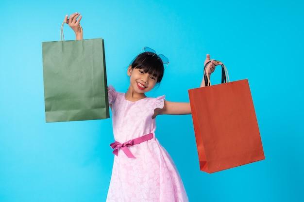 Szczęśliwego młodego azjatyckiego dziewczyna dzieciaka mienia elegancki torba na zakupy, styl życia opłacony dla dzieciak mody stylu pojęcia