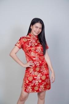 Szczęśliwego nowego chińskiego roku. piękna azjatycka kobieta ubrana w tradycyjną sukienkę qipao cheongsam z gestem gratulacji na białym tle na jasnoszarej powierzchni z miejsca na kopię
