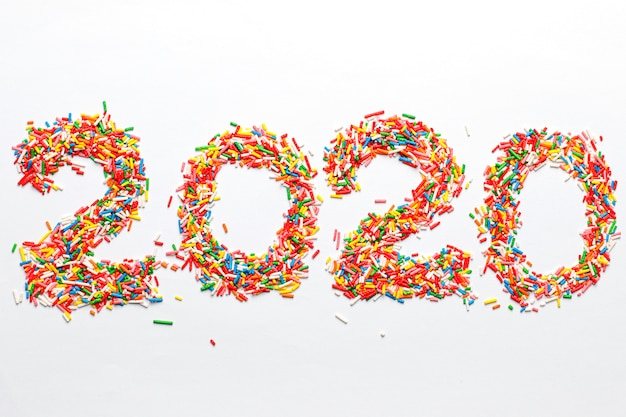 Szczęśliwego nowego roku 2020. kolorowy numerowy kształt z jaskrawym tęczowym cukierem kropi odosobnionego na bielu