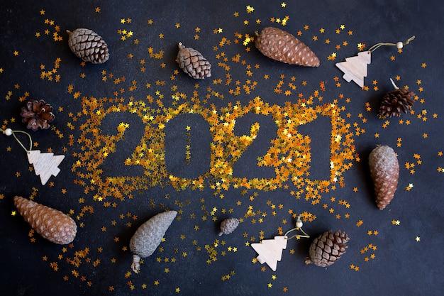 Szczęśliwego nowego roku 2021. błyszczące gwiazdy na czarnej powierzchni z szyszkami