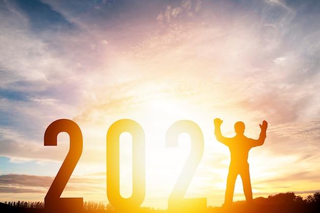 Szczęśliwego nowego roku 2021 koncepcja sylwetki człowiek stojący z numerem z pięknym pomarańczowym niebem na zmianę na nowy rok 2021.