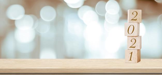 Szczęśliwego nowego roku 2021 na bloku drewna i rozmycie tła światła streszczenie bokeh