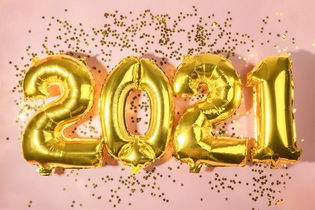 Szczęśliwego nowego roku 2021. świąteczny złoty balon metaliczny z numerami 2021 i konfetti w gwiazdki