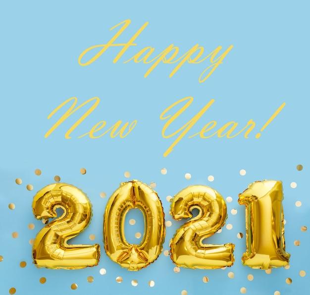 Szczęśliwego nowego roku 2021 tekst ze złotymi balonami foliowymi 2021 na niebieskim tle z konfetti. kwadratowy plon.