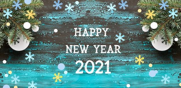 Szczęśliwego nowego roku 2021 tło z gałązek jodły i papierowych dekoracji.