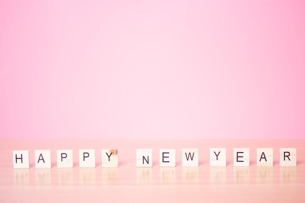 Szczęśliwego nowego roku 2021 z drewnianą kostką na różowym tle.