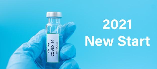 Szczęśliwego nowego roku 2021 z fiolką ze szczepionką covid-19 przeciwko zakażeniu koronawirusem w ręce lekarza