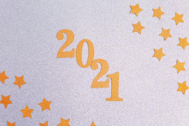 Szczęśliwego nowego roku 2021 z gwiazdami ze złotego brokatu na jasnym tle. dekoracja świąteczna. obchody nowego roku. tło wakacje