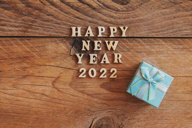 Szczęśliwego nowego roku 2022. cytat wykonany z drewnianych liter i cyfr 2022 na drewnianym tle z niebieskim pudełkiem smal. kreatywna koncepcja na nowy rok kartkę z życzeniami