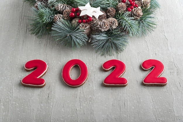 Szczęśliwego nowego roku 2022. czerwone ciasteczka imbirowe i wieniec świąteczny. jasnoszara ściana na tle.