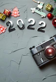 Szczęśliwego nowego roku 2022 ozdoby świąteczne i gałęzie na szarym betonowym tle