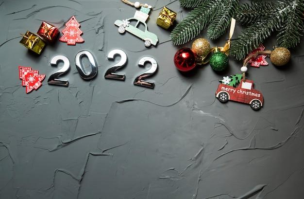 Szczęśliwego nowego roku 2022 symbol liczby 2022 ozdoby świąteczne i gałęzie na szarym betonie