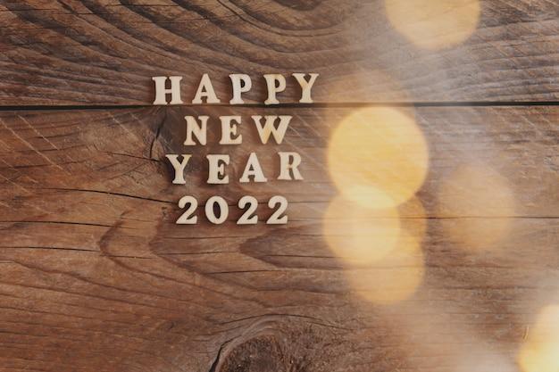 Szczęśliwego nowego roku 2022. symbol z drewnianych liter i cyfr 2022 na drewnianym tle ze złotym bokeh