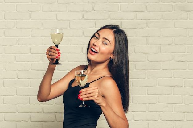 Szczęśliwego nowego roku dla ciebie, jedna młoda i piękna kobieta tańczy z lampką szampana