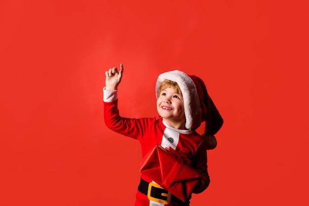Szczęśliwego nowego roku dzieci boże narodzenie dziecko z prezentem bożonarodzeniowym szczęśliwe dziecko w stroju świętego mikołaja trochę