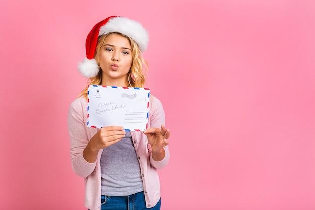 Szczęśliwego nowego roku i świąt! śliczne małe dziecko nastolatek blondynka z listem do świętego mikołaja