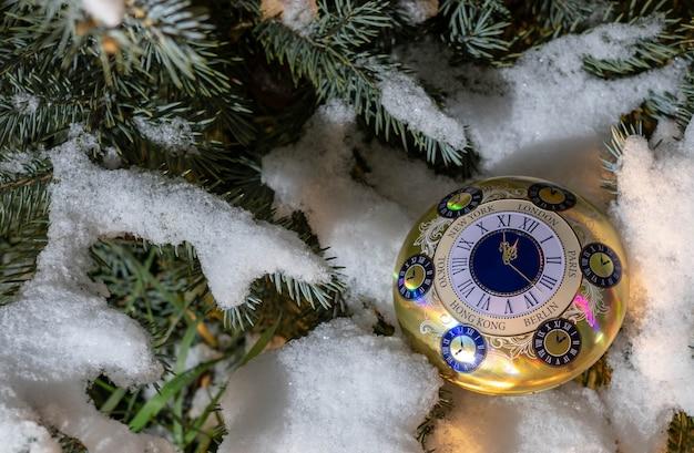 Szczęśliwego nowego roku i wesołych świąt, budzik na tle choinki.
