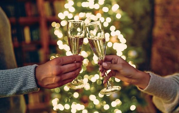 Szczęśliwego nowego roku i wesołych świąt! kieliszki z szampanem w rękach z gratulacjami. choinka z girlandami na tle.