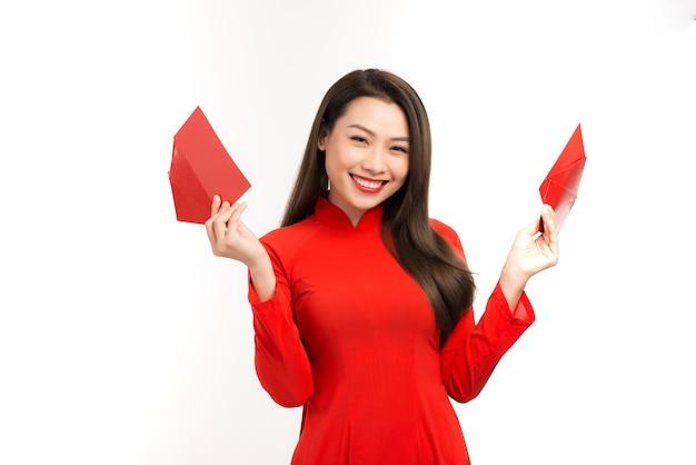 Szczęśliwego nowego roku księżycowego, młoda wietnamska kobieta w tradycyjnej czerwonej sukience ao dai trzyma czerwoną kopertę na białym tle.