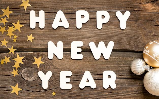 Szczęśliwego nowego roku litery i kulki i gwiazdy na drewnianym tle.